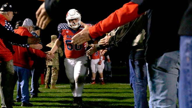 """Lincoln player Austin Reimer high-fives current military members and veterans as the team takes the field before the """"Raiders Salute"""" football game between Lincoln High School and D.C. Everest  School High School in Wisconsin Rapids, Wis., on October 13, 2017."""