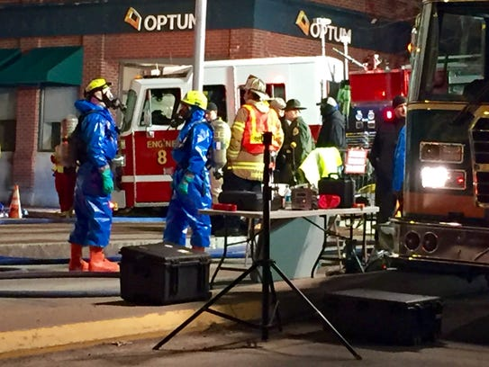 Emergency workers don protective gear outside an apartment