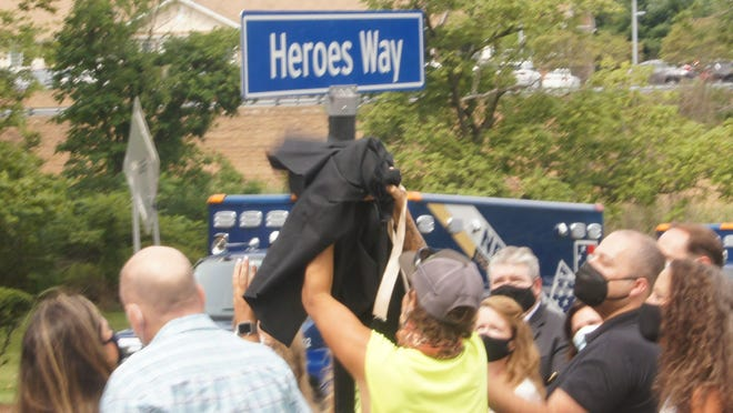 A Newton DPW worker pulls off a black covering to reveal the new street name (Heroes Way) for the entrances to Newton Medical Center during ceremonies on Thursday, Aug. 13, 2020 to honor first responders, essential workers and medical staff who are the front line in the fight against the coronavirus pandemic.