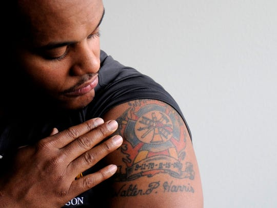 James Hill-Harris shows off a tattoo in honor of his adopted dad, Walter P. Harris, left, who died in the line of duty while fighting an arson fire in 2008.
