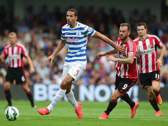 Queens Park Rangers' Rio Ferdinand, left, battles for the ball with Sunderland's Steven Fletcher during their English Premier League soccer match at Loftus Road, London, Saturday, Aug. 30, 2014. (AP Photo/Adam Davy, PA Wire)    UNITED KINGDOM OUT    -   NO SALES    -    NO ARCHIVES