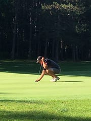 Connor Jakacki surveys the green before making a putt during a summer tournament. He is a senior at Livonia Stevenson and will play for Spartans next spring.