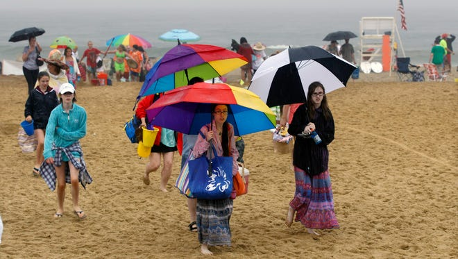 """People pack up and leave the beach in the rain during the """"NJ Sandcastle Contest,""""  contest in Belmar, N.J., Wednesday, July 15, 2015. After nearby lightning strikes during a steady rain, the beach patrol stopped the competition and asked everyone to leave the beach. (AP Photo/Mel Evans)"""