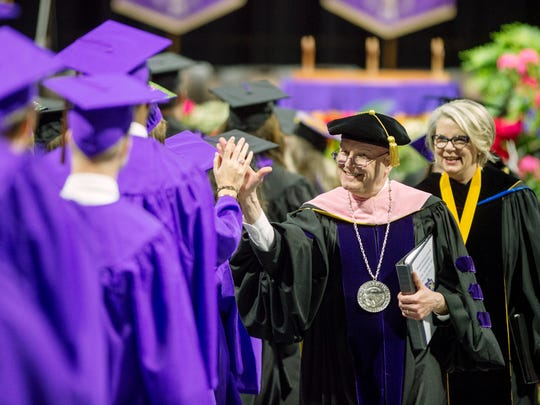WCU Chancellor David O. Belcher, accompanied by Margaret Spellings, president of the UNC System, greets graduating students with a high-five during a commencement ceremony in December 2017.