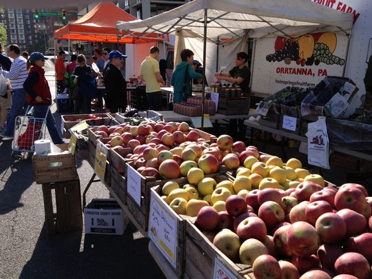 Customers buy fruit from a farmers' market.
