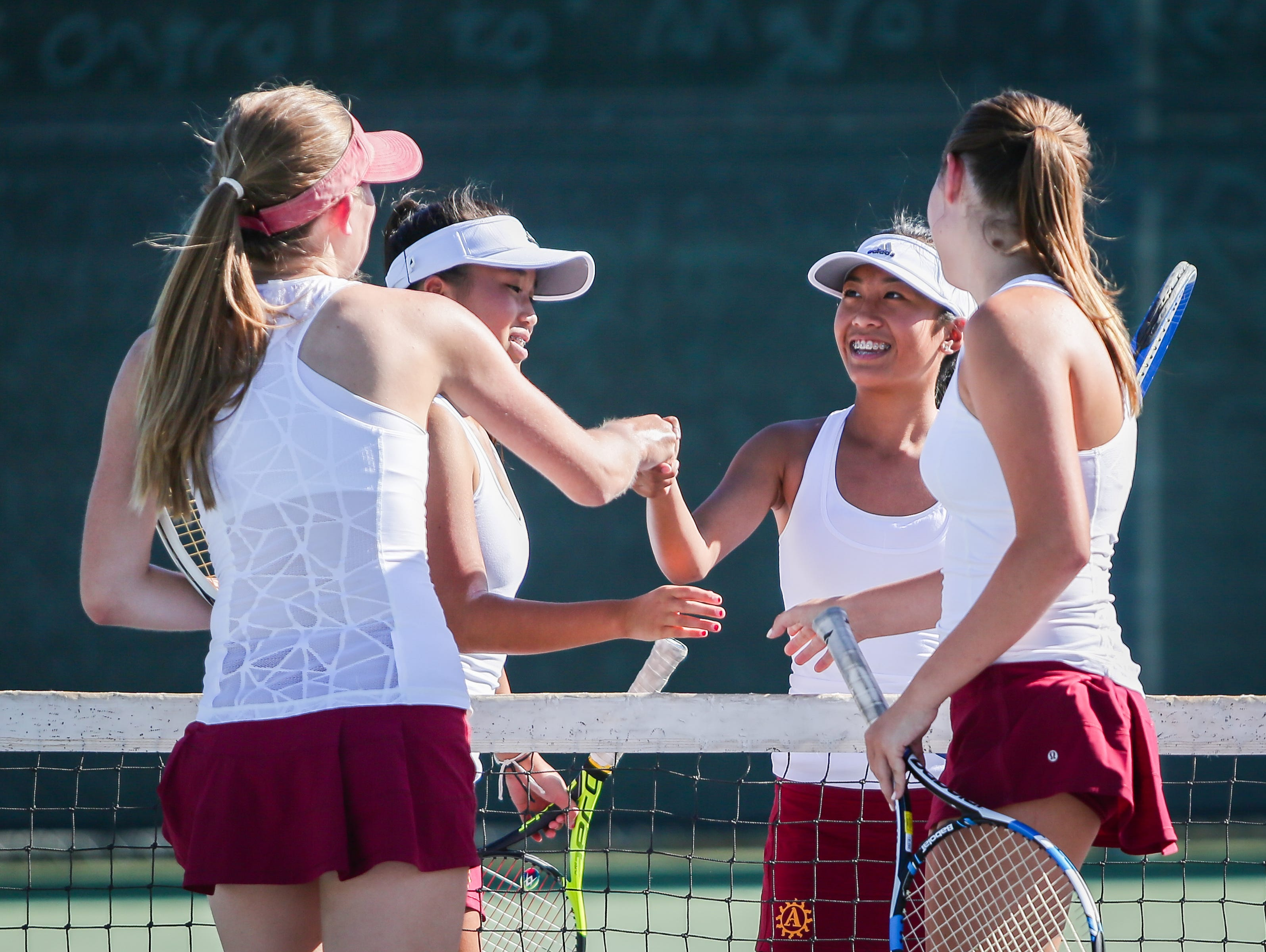 Players congratulate each other after a doubles set Tuesday as Palm Desert defeated La Quinta 12-6.