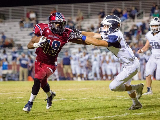 Derrick Kennedy stiff arms a Redlands defender on his