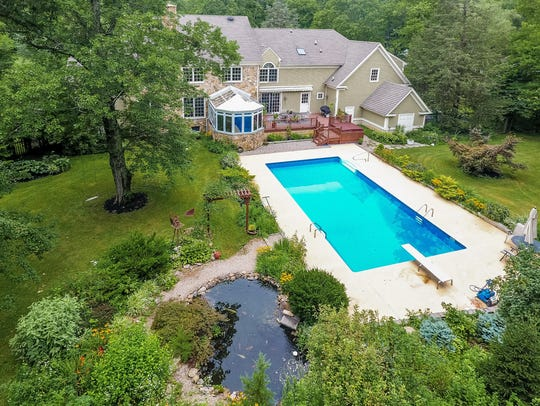 In  the rear yard are a swimming pool, a koi pond,