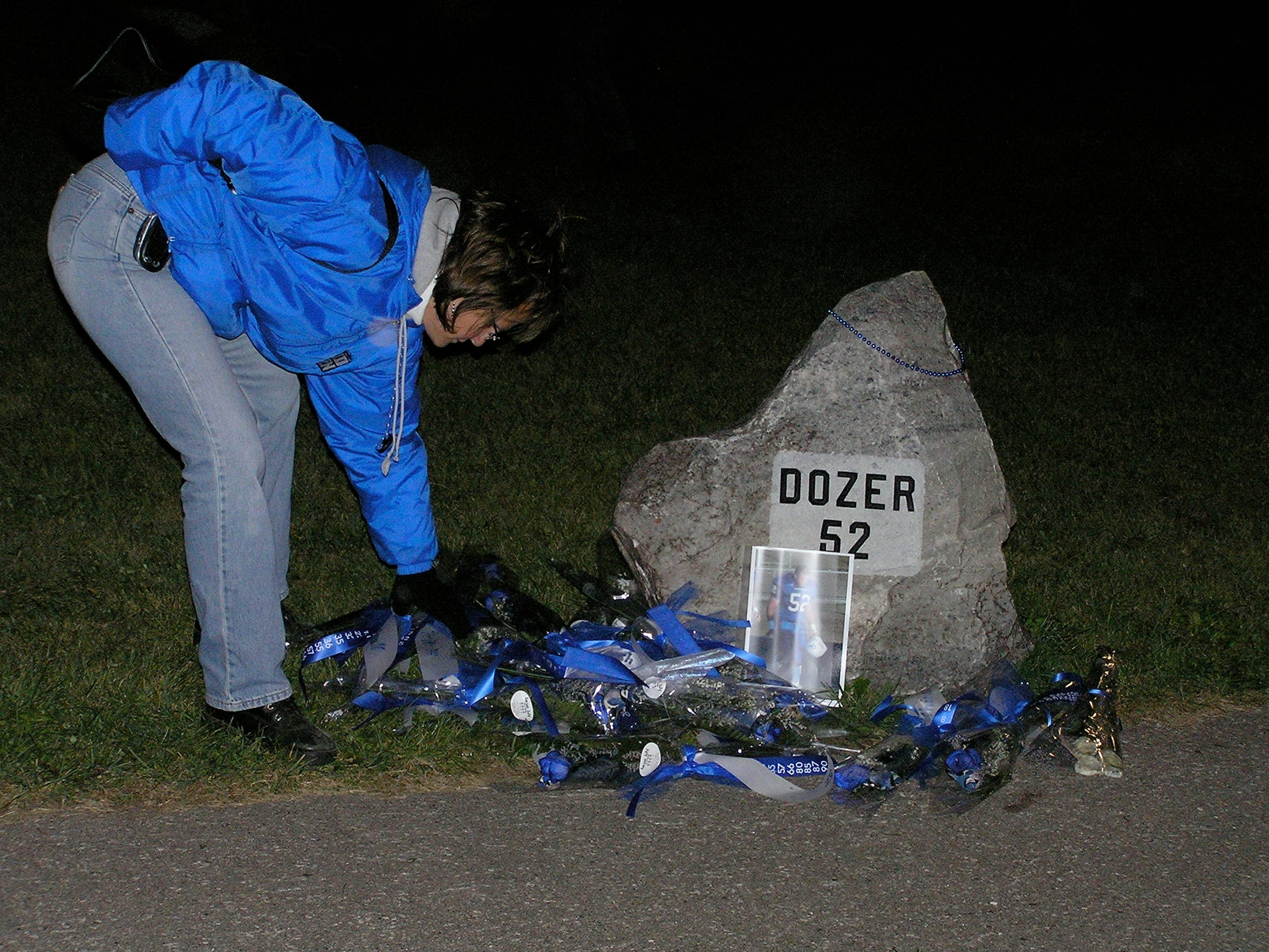 At a 2004 Cambridge High School football game. flowers are placed alongside a rock dedicated to Dustin Zuelsdorf near the field.