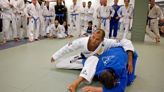 Legendary Brazilian Jiu-Jitsu and mixed-martial arts  fighter Royce Gracie, left, grapples with trainer Jon Burke, of Orlando, during a lesson at a seminar at The MMA Lab in Glendale in 2008.