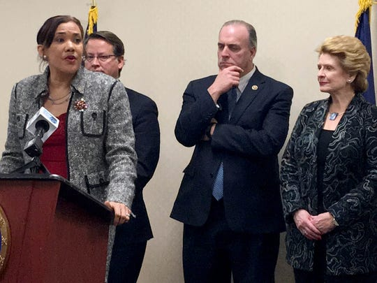 Flint Mayor Karen Weaver is at the podium in the background is U.S. Sen. Gary Peters, U.S. Rep. Dan Kildee, and U.S. Sen. Debbie Stabenow. They are at the University of Michigan-Flint's Riverfront Banquet Center Thursday, Dec. 15, 2016 for a press conference regarding the recently-passed legislation declaring $170 million in federal assistance for lead-contaminated cities following Flint's water crisis.