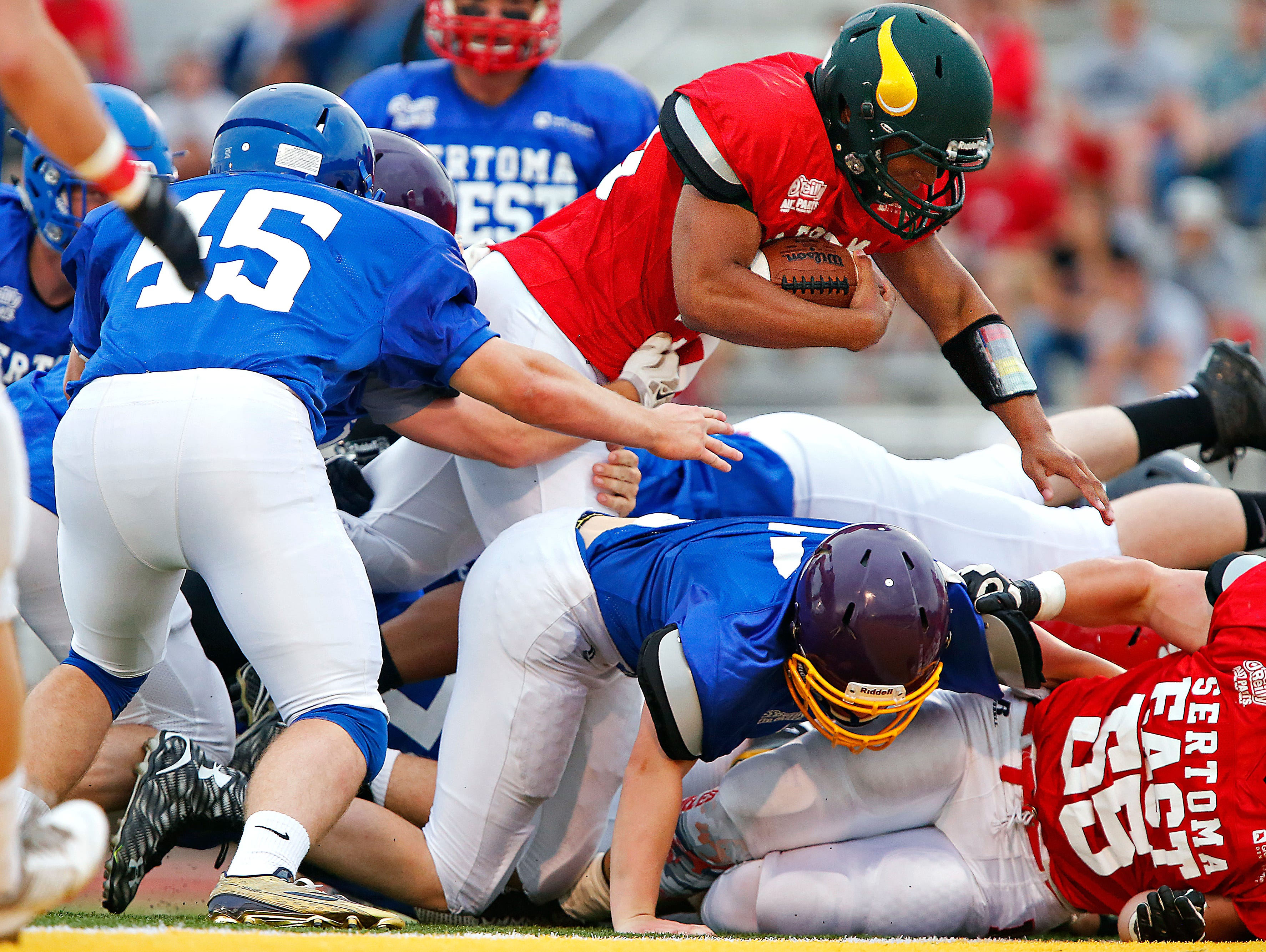 East All-Stars running back Anthony Riley (33) leaps over a defender to score a touchdown during first quarter action of the Sertoma Grin Iron Classic football game held at JFK Stadium in Springfield, Mo. on June 3, 2016.