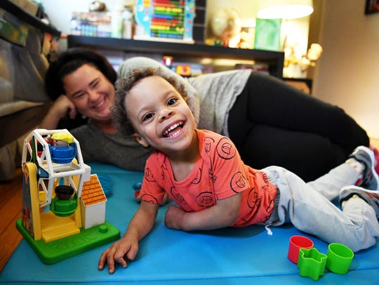 Solomon Hope smiles as he plays with his mother, Sarah