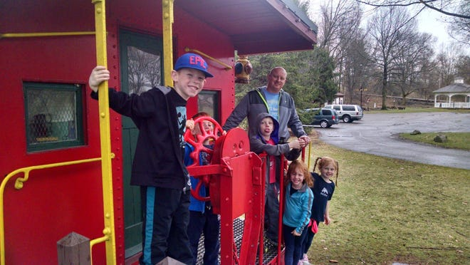 Adam Greenslade stands on the back of a caboose with his five children.