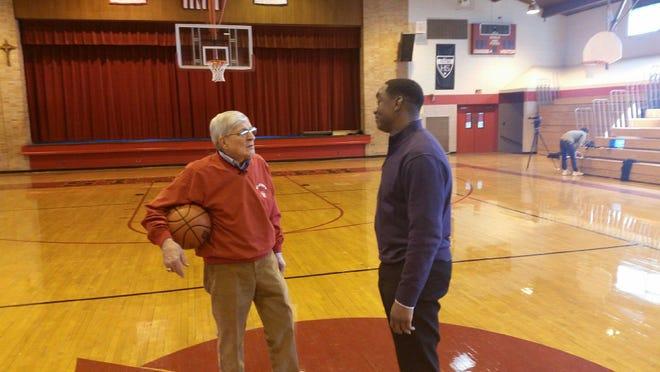 Legendary coach Gene Pingatore and legendary NBA guard Isiah Thomas chat on the basketball court.
