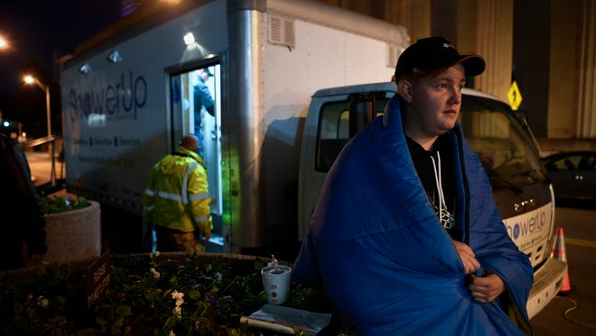 Damon Sanderson, 24, waits for a haircut outside a mobile shower truck for the homeless parked on Seventh Avenue on Monday, Oct. 23, 2017, in Nashville.