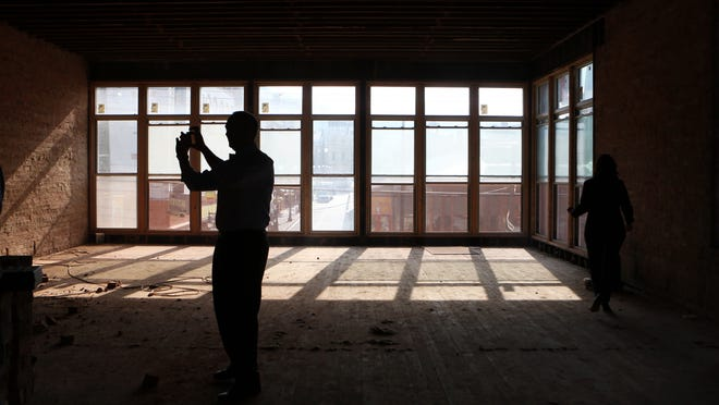 Eric Avner of People's Liberty takes photos of the progress of their office space on Elm Street near Findlay Market.