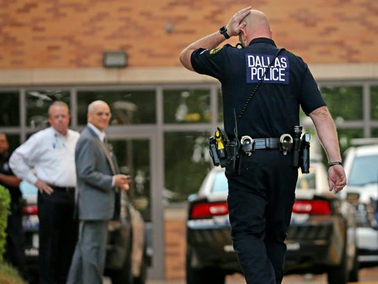 A Dallas Police officer walks to the entrance of the