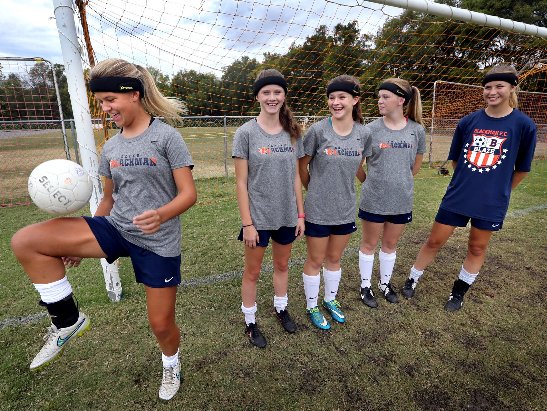 Blackman's Kenzi Vetter, a sophomore, left juggles the soccer ball while wearing a headband that all Blackman girls soccer players must wear before getting on the field for either a game or practice, on Monday, Sept. 28, 2015, before a game against Smyrna. The headbands are suppose to lessen the chances of receiving a concussion. Vetter's teammates (L to R) Katelyn Davis, a freshman, Emily Nash, a junior, Mallory Conlin, a sophomore, and Amelia Goodnight, a junior stand behind Vetter as she juggles the ball and are all wearing the same headband.
