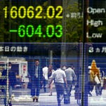 People are reflected on the electronic board of a securities firm in Tokyo, Monday, May 2, 2016. Asian stock markets fell Monday as investors displayed their disappointment over the lack of further stimulus from Japan's central bank.