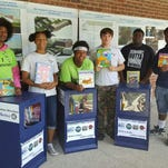 YouthBuild/AmeriCorps students William Artist Jr., left to right, Grenisha Meekins, Taquan Pesante, Damien Cole, Jahi Norwood and Stefan Jackson are shown with some of the refurbished newspaper honor boxes that are now homes for books.