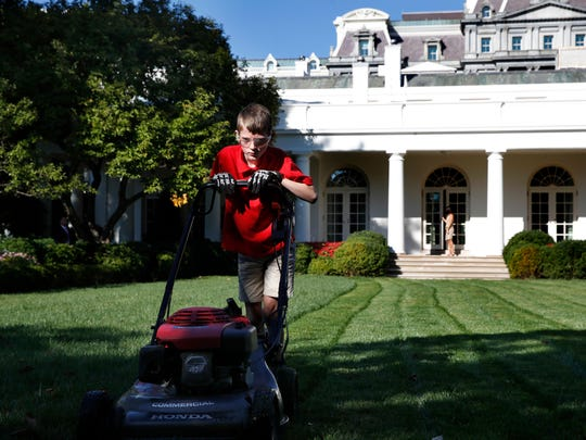 Frank Giaccio, 11, of Falls Church, Va., is focused as he mows the lawn of the Rose Garden, Friday, Sept. 15, 2017, at the White House in Washington. The 11-year-old wrote President Donald Trump requesting to mow the lawn at the White House. (AP Photo/Jacquelyn Martin)