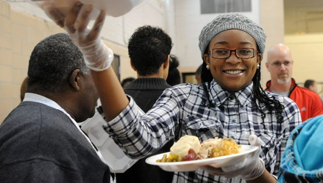 Teccorra Bracy, a Harding High School student and member of Harding's UNITY group, weaves her way through traffic to serve plates full of food to those attending the annual Interdenominational Ministerial Alliance Thanksgiving dinner.