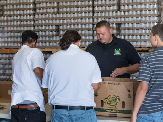Dennis Sandoval, facing the camera, works with students from Courage to Change as they cull cantaloupes for distribution at Food Link in Exeter on Monday, August 20, 2018.