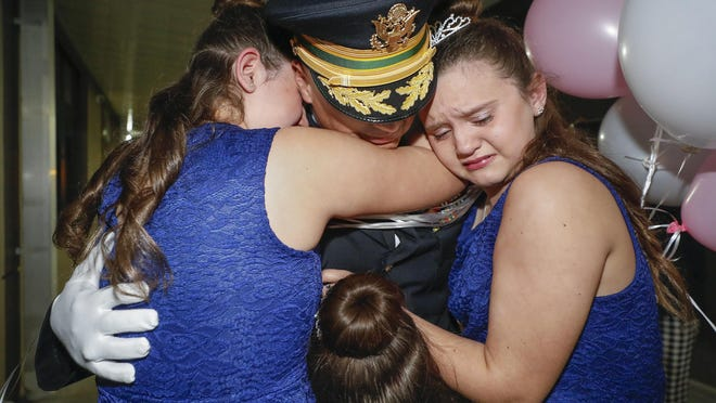 U.S. Army Chief Warrant Officer James Ring gets emotional hugs from his three daughters -- Faith, 11, Grace, 7, and Hope, 11 -- during his surprise return from deployment to attend the Father/Daughter Dance at McKeel Academy in Lakeland on Friday night.