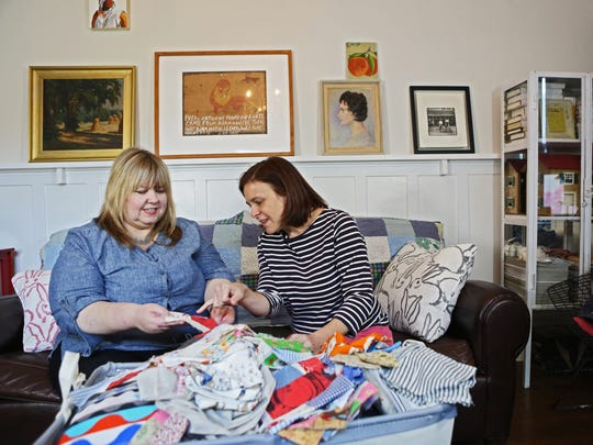 "Andria Lisle, left, and Amie Petronis Plumley look at fabric at Lisle's Midtown home on Thursday. The women are best-selling Memphis authors reviving the art of sewing and quilting for kids. Their latest book is called ""Sewing School Quilts: 15 Projects Kids Will Love to Make."""