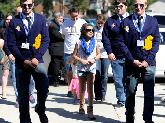 Emily Sobeck, center, is escorted into Royal Oak's