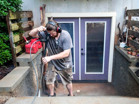 Shawn Johnson pressure washes a house in West Asheville