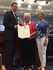Martin County Commissioner Doug Smith presents the 80th anniversary proclamation to Donna Berger and Bobbie England of the Stuart Garden Club.