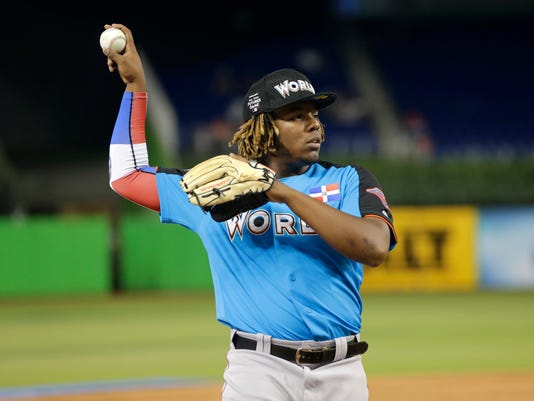 FILE - In this July 9, 2017, file photo, World Team designated hitter Vladimir Guerrero Jr., of the Toronto Blue Jays, warms up before the All-Star Futures baseball game, in Miami. Two sons of former big leaguers top Toronto's list of prospects. Shortstop Bo Bichette and third baseman Vladimir Guerrero Jr. (AP Photo/Lynne Sladky, File)