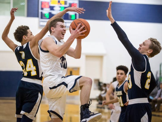 Marysville's Ross Hinkley goes for a shot over a host
