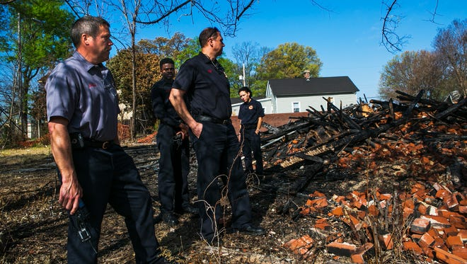 "March 28, 2017 - (From left to right) Lt. Keith Culp, Matthew Taylor, Megan Clark, and driver John Murley, fire fighters with the Memphis Fire Department, survey damage from a house fire at 975 Peabody Ave. on Tuesday morning. ""It was amazing how fast the building was burning. The wind had a lot to do with it, but being this old, it went up very fast. Complete loss. Really sad,"" Culp said of the fire that occurred Saturday afternoon. Culp brought his crew out to the scene three days later for learning purposes. ""These guys were off on Saturday, so we like to review what went right and how we can improve our service and stay safe and go home and protect the citizens."""