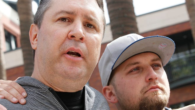 Robert Preece and Robert Preece Jr., father and brother of Jonathan Denver, make a public plea for witnesses to Wednesday's fatal stabbing of Jonathan Denver, during a news conference outside AT&T Park before the Giants' baseball game in San Francisco on Sunday.