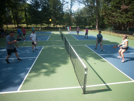 Pickleball players gather as the play at the Lion's Den courts in Cherry Hill.