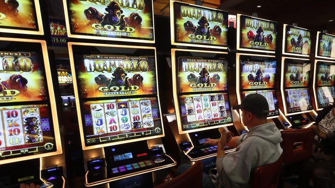 A man plays a slot machine at the MGM Grand Detroit casino in Detroit, Wednesday, March 11, 2020.