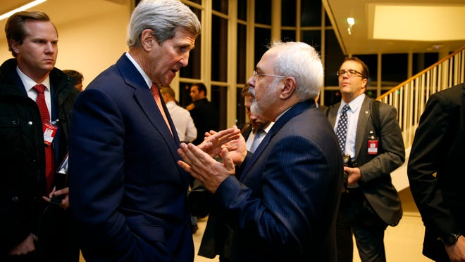 In this Jan. 16, 2016 file photo, Secretary of State John Kerry talks with Iranian Foreign Minister Mohammad Javad Zarif in Vienna, after the International Atomic Energy Agency (IAEA) verified that Iran had met all conditions under the nuclear deal.