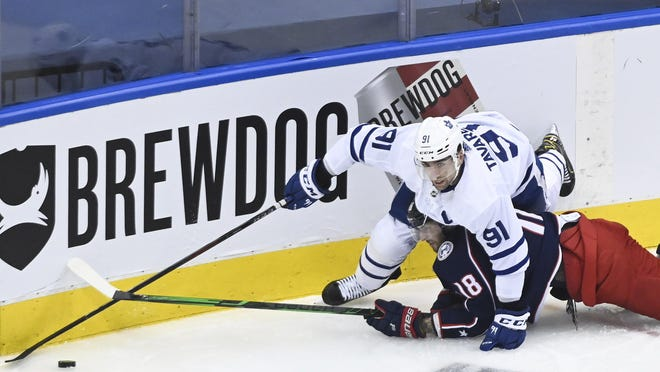 Toronto Maple Leafs center John Tavares (91) battles for the puck against Columbus Blue Jackets center Pierre-Luc Dubois (18) in front of a BrewDog advertisement during the second period of their NHL playoff game Aug. 6 in Toronto.