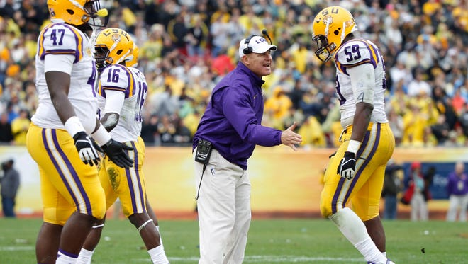 LSU head coach Les Miles congratulates Tigers defensive end Jermauria Rasco (59) and teammates during the Outback Bowl against the Iowa Hawkeyes last season. LSU won, 21-14.