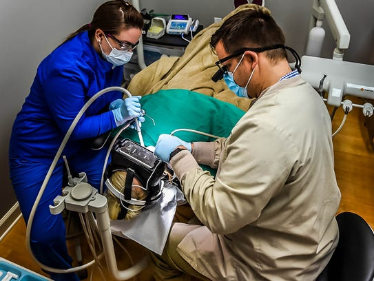 Dr. Matt Palomaki, right, works on a patient during