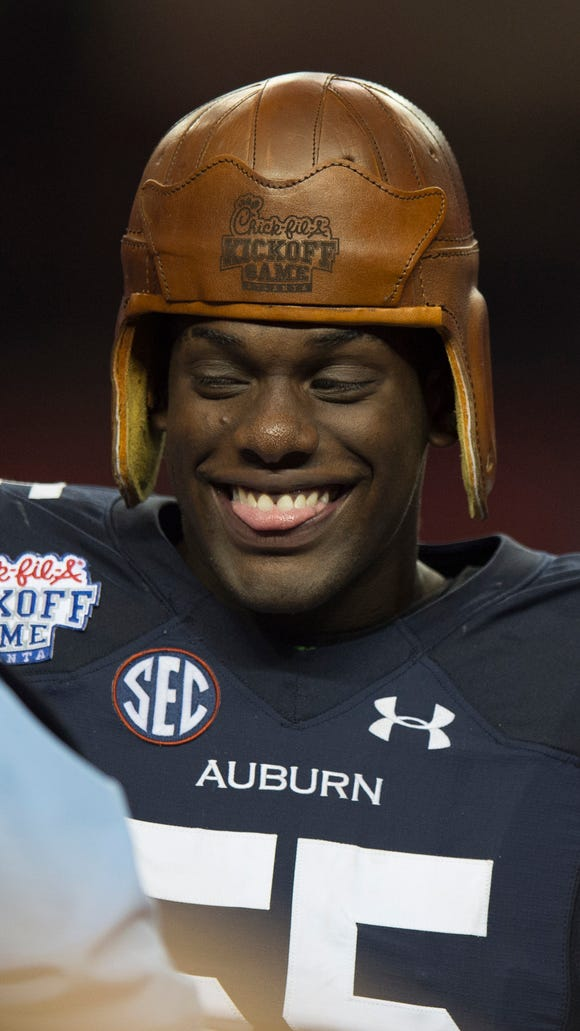 Auburn defensive lineman Carl Lawson (55) wears the leather helmet after Auburn defeated Louisville 31-24 on Saturday, Sept. 5, 2015, in at the Georgia Dome in Atlanta, Ga.