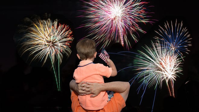A father and son watch Fourth of July fireworks at the Scottsdale Princess.