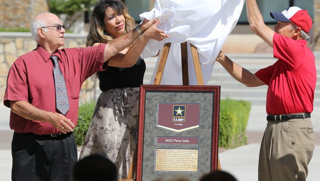 Family members of Medal of Honor recipient Army Master Sgt. Michael Pena unveil a marker for the gate renamed in his honor Tuesday at Fort Bliss. Six of the post's gates were named after soldiers who have a connection to the Borderland or the 1st Armored Division. The family members are son Michael Pena Jr., daughter Vicky Pena and nephew Rick Pena.