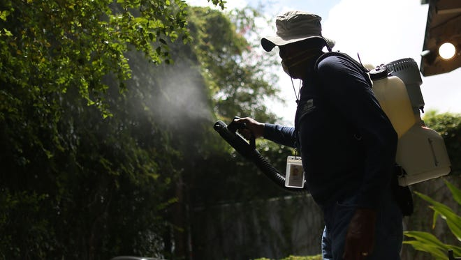 Man sprays mosquito pesticide in Miami on August 1, 2016.