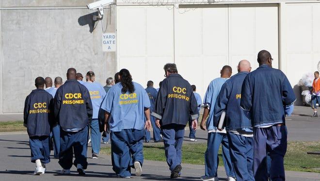 In this Feb. 26, 2013, file photo, inmates walk through the exercise yard at California State Prison Sacramento near Folsom.