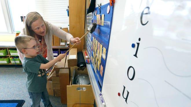 Kindergarten teacher Julie Wilson helps Milo Fosberry point at letters during a spelling class at Jefferson Road Elementary School.
