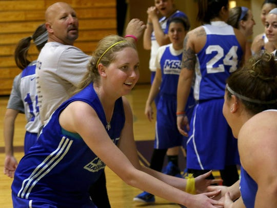 FILE - In this Oct. 23, 2014, file photo, Lauren Hill, left foreground, slaps hands with teammates as she practices with her NCAA college basketball team at Mount St. Joseph in Cincinnati. The 19-year-old freshman basketball player died at a hospital in Cincinnati Friday, April 10, 2015, the co-founder of her foundation The Cure Starts Now said. (AP Photo/Tom Uhlman, File)
